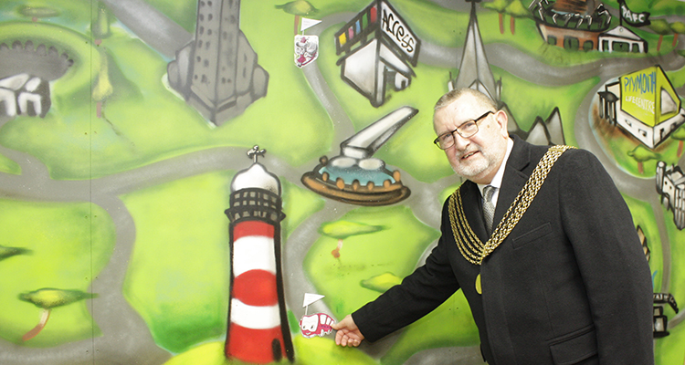 Plymouth Mayor places a sticker on Friends of Access Plymouth board
